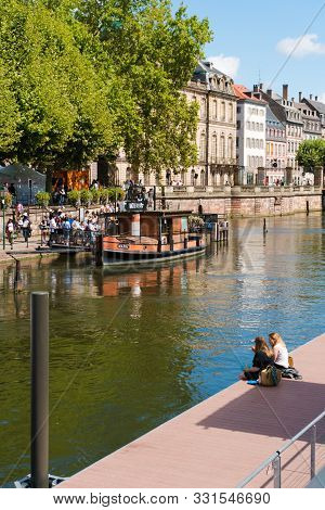 Tourists Waiting To Board A Boat For A Sightseeing Cruise On The Canals Of Historic Strasbourg