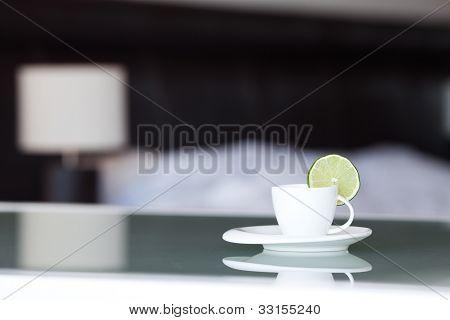 Tee mit Zitrone, im Hintergrund das Bett und die Lampe