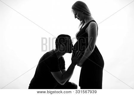 Silhouette Portrait Of Husband Man Kissing Pregnant Woman Belly.