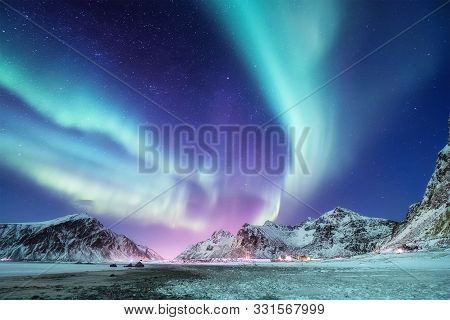 Aurora Borealis On The Lofoten Islands, Norway. Green Northern Lights Above Mountains. Night Winter