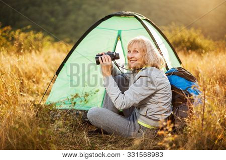 Senior Woman Is Camping In Mountain. Active Retirement.