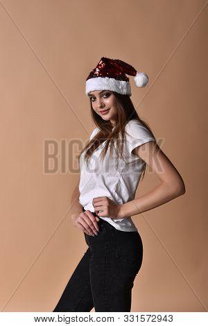 Beautiful Female Model Wear Santa Hat. Girl In Santa Hat. Young Girl In Santa Claus Hat Posing In St