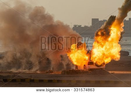 Military Strike Or Bomb In War On A Car Causes Fire Ball And Explosion In The Town In Chaos. Militar
