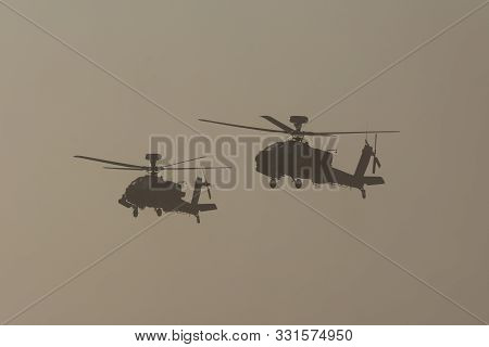Two Military Choppers In Combat And War Flying Into The Smoke And Chaos And Destruction. Military Co
