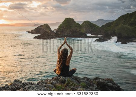 Young Woman Practicing Yoga At Sunset With Beautiful Ocean And Mountain View. Sensitivity To Nature.