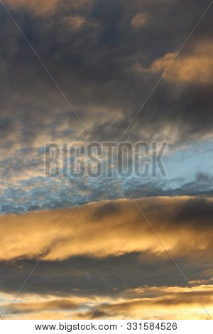 Early Morning Skies At Daybreak, With Gold And Blue Color Of Heavy Cloud Cover Beginning To Break Aw