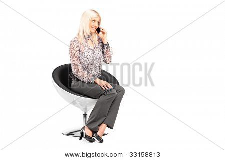 A young woman sitting on a chair and talking on a mobile phone isolated on white background