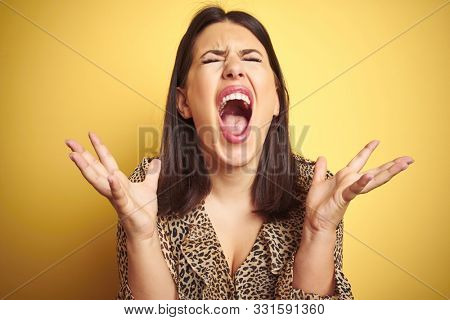 Young beautiful brunette woman wearing leopard shirt over yellow isolated background crazy and mad shouting and yelling with aggressive expression and arms raised. Frustration concept.