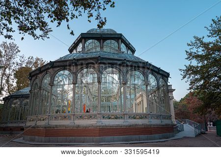 Sunset View Of Crystal Palace Or Palacio De Cristal In Retiro Park In Madrid, Spain.