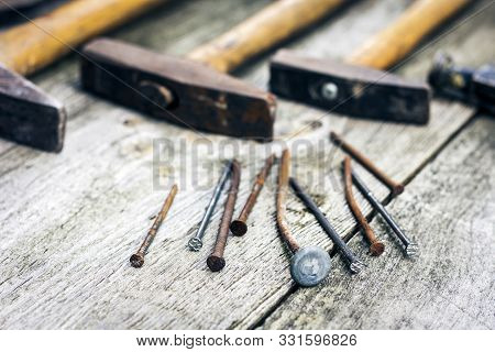 Set Of Vintage Hand Construction Tools Hammers With Nails On A Wooden Background, Retro Concept