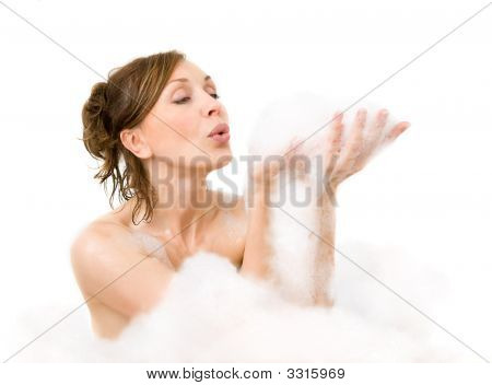 Attractive Woman Blowing On Foam In Her Hand