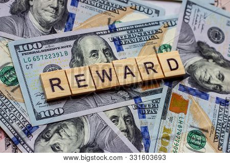 The Word Reward On Dollar Usa Background. Rewarding And Financial Bonus Concept.