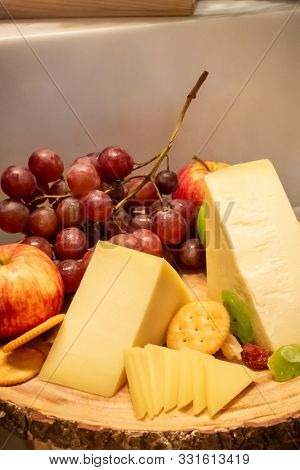 gruyere cheese with variety of fruit and cracker on wooden plate in buffet line