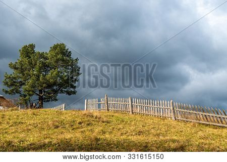 Landscape With Lonely Tree With Village Fencing And Dark Stormy Sky