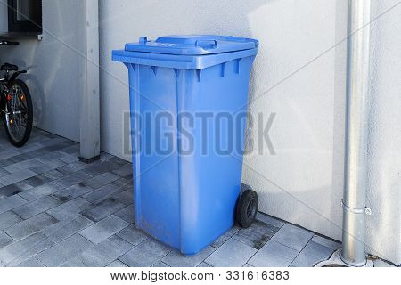 Blue Plastic Trash Can In Europe. Household Trash, Storage On The Street Near The Wall In One Blue T