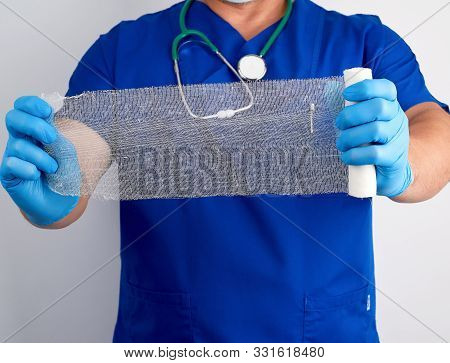 Doctor In Blue Uniform And Latex Gloves Holds A Roll Of White Bandage For Dressing Gauze Wounds, Whi