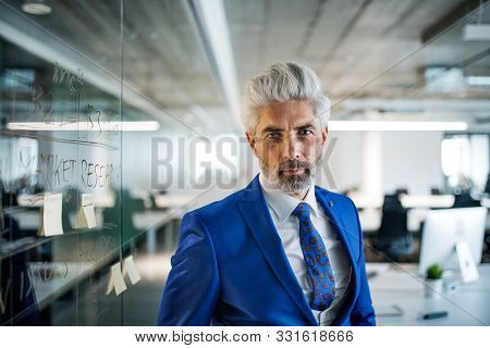 A Portrait Of Mature Businessman Standing In An Office, Looking At Camera.