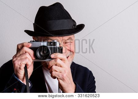 Portrait Of A Senior Man With Hat And Camera In A Studio, Taking Photograph.