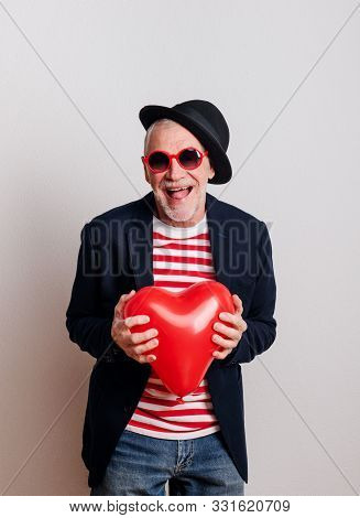 Portrait Of A Senior Man In Love In A Studio, Holding A Red Heart Balloon.