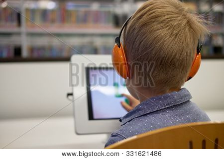 Elementary School Boy Sitting In Library, Using Touchscreen Computer For Education