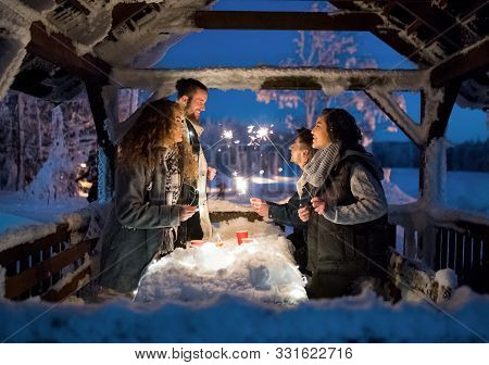 Group Of Young Friends Outdoors In Snow In Winter At Night, Holding Sparklers.