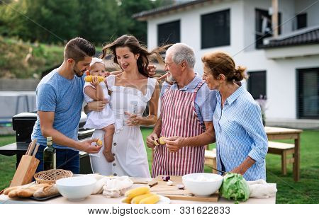 Portrait Of Multigeneration Family Outdoors On Garden Barbecue.