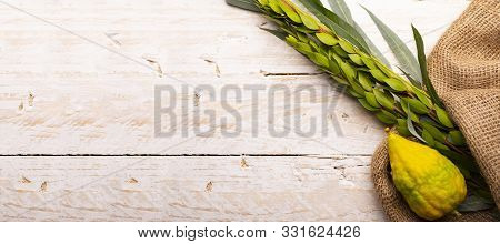 Top View On Sukkot Festival Symbols: Palm, Willow, Myrtle, Etrog. Lulav On Jute Fabric And Light Woo