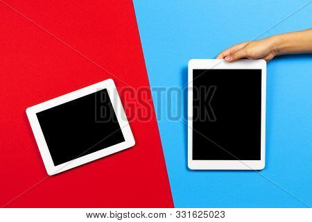 Kid Hand With Tablet Computer On Red And Light Blue Background