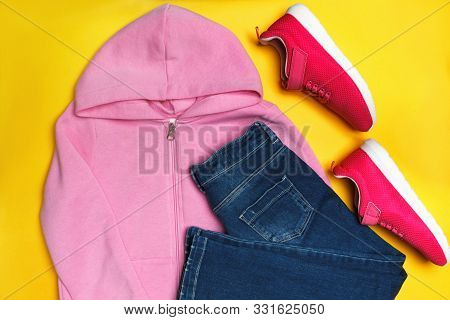 Top View Of A Composition Of Casual Clothes For A Girl On A Yellow Background. Sweatshirt, Jeans, Sn