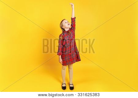 A Small Child Measures Her Growth On A Yellow Background. Full-length Girl In A Red Dress. Developme