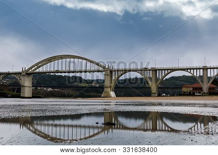 A Big Bridge With Its Reflections In The Sand