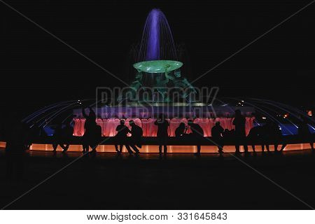 Silhouettes Of People Sitting Near Triton Fountain In The Central Square Of Valletta With Night Colo
