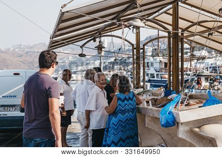 Mykonos Town, Greece - September 20, 2019: Women Chatting While Queuing To Buy Fresh Fish From A Str