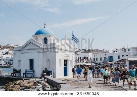 Mykonos Town, Greece - September 23, 2019: People Walking Past Agios Nikolakis Church In New Port In