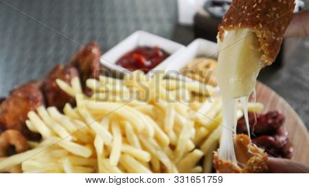 Wooden Board With French Fries, Cheese Sticks, Onion Rings, Fried Chicken Wings, Smoked Sausages Wit