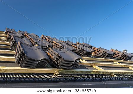 Roof Ceramic Tile Arranged In Packets On The Roof On Roof Battens. Preparation For Laying Roof Tiles
