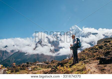 Young Hiker Backpacker Man Using Trekking Poles Enjoying The Thamserku 6608m Mountain During High Al