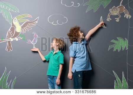 Boys Walking Through Tropic Forest. Two Brothers Feeding Beautiful Exotic Birds And Monkey Drawn Wit
