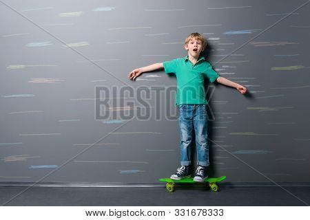 Skateboarder Drives On High Speed. Young Boy With Frightened Face Riding On A Green Skateboard And L