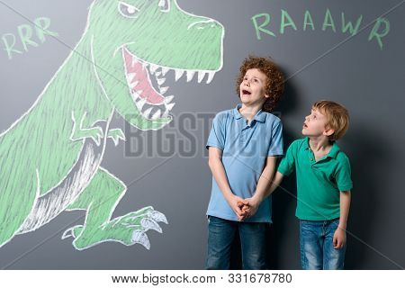Frightened Boys And Enormous Dinosaur. Brothers Screaming And Looking On Jaws Of The Growling Reptil