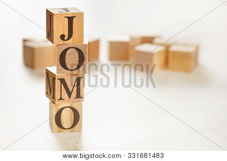 Four Wooden Cubes Arranged In Stack With Text Jomo Meaning Joy Of Missing Out On Them, Space For Tex