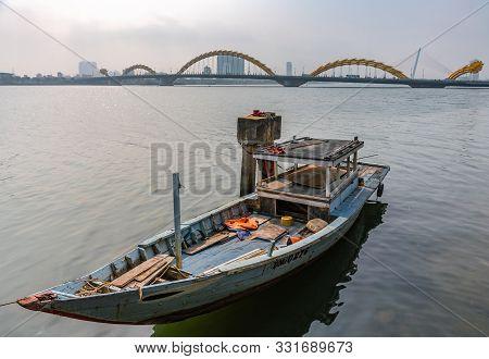 Da Nang, Vietnam - March 10, 2019: Sloop On Wide Han River And Cau Rong Or Dragon Bridge On Horizon