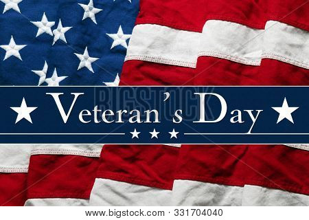 Veteran's Day text with stars over wavy USA American flag
