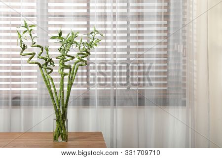 Vase With Bamboo Stems On Wooden Table Indoors, Space For Text