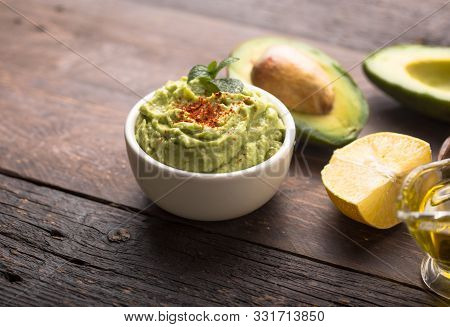 Green Hummus. Bowl Of Green Hummus, Delicious Cream Of Chickpeas And Avocado On A Wood Background.