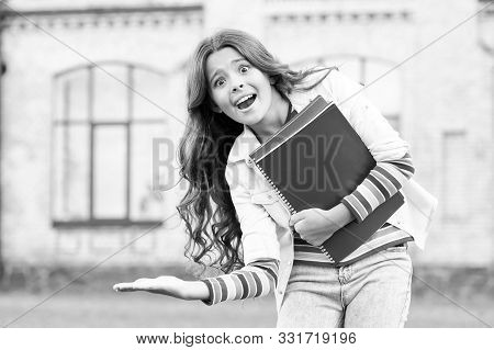 Product Advertising. Happy Small School Age Child Presenting Your Product. Little Girl With Books Sm