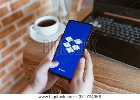 Chiang Mai, Thailand - Oct.18,2019: Woman Holding Xiaomi Mi Mix 3 With Dropbox On Screen At Coffee S