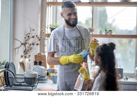Beaming Father Taking Detergents While Cleaning Kitchen With Daughter