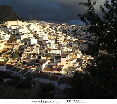 Dark Clouds And Sunshine Over Andalusian Village