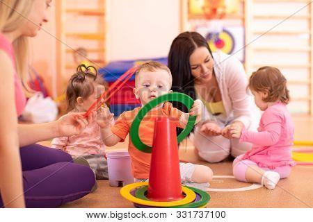 Children Doing Physical Activities With Nursery Teacher In Kindergarten Or Creche